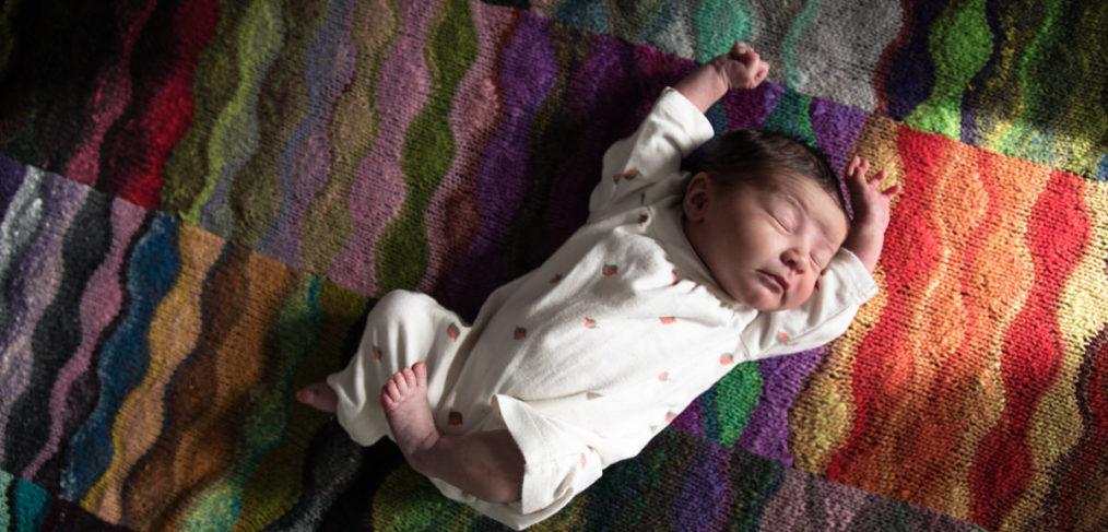 Newborn Baby on Rainbow Blanket