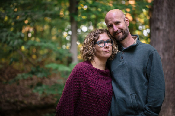 Husband and wife smiling at camera in woods.