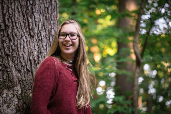 Teen girl laughing, leaning against tree.
