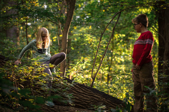 Girl and boy playing in the woods.
