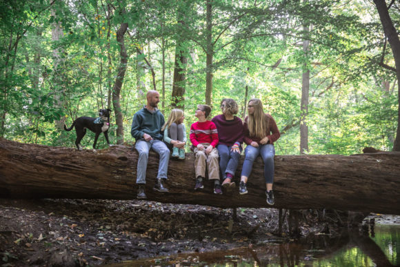 Family and dog sitting on log in the woods.