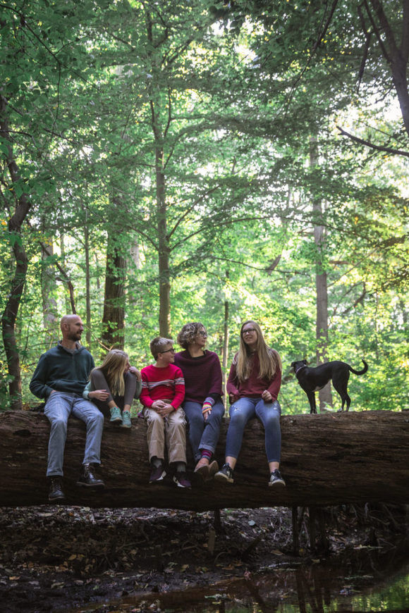 Family sitting on log together in Saddlers Woods, Haddon Township, NJ.