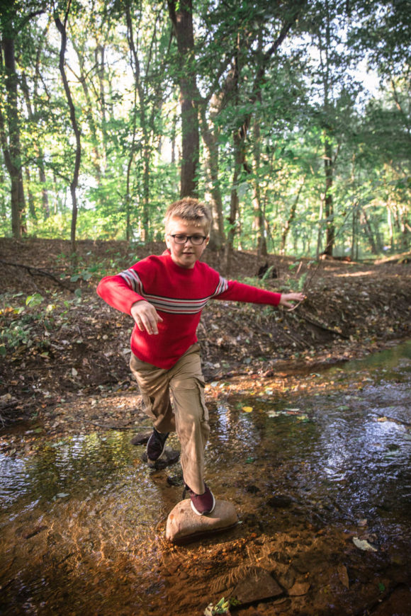 Boy crosses creek on stepping stones.