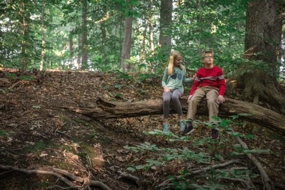 Brother and sister sitting on log together.