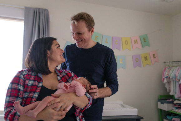 Mother and father hold baby in nursery.