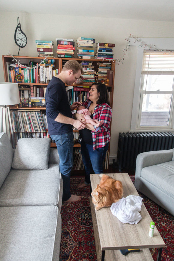 Mom and dad holding newborn in living room.