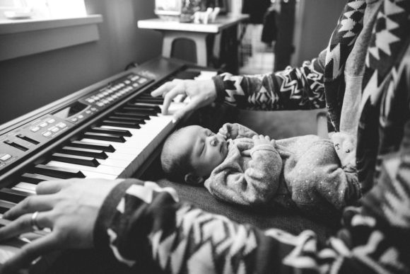 Father plays piano with baby on lap.
