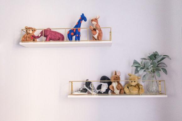 Detail of baby items on wall shelf in nursery.