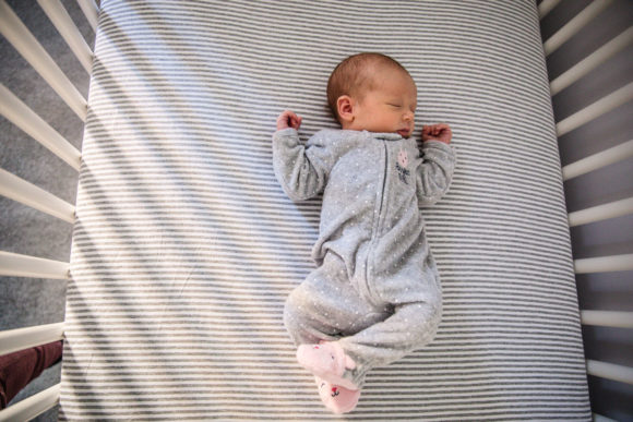 Baby laying in crib on striped sheets.