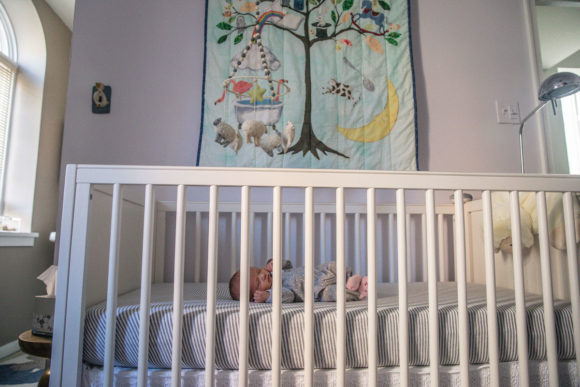 Baby lays in crib under quilt on wall.