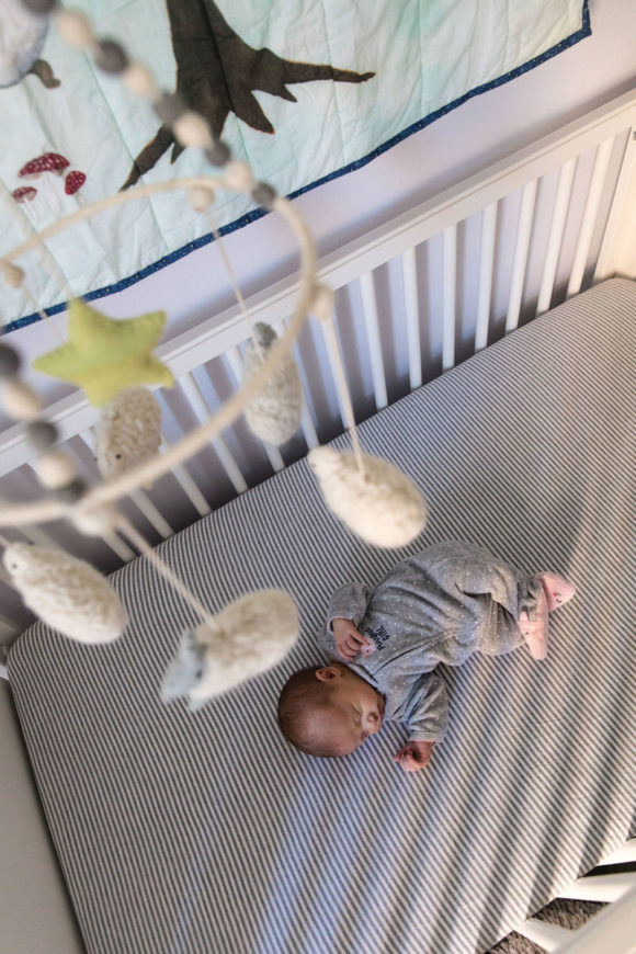 Overhead photograph of baby in crib with mobile.