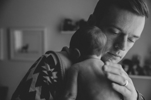 Father holding newborn baby on shoulder.