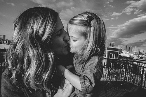 Mother kisses little girl.