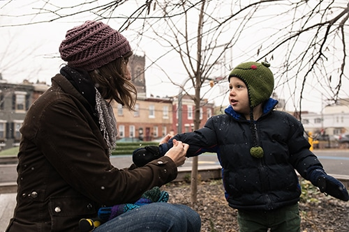 Mother helps child put on mitten.