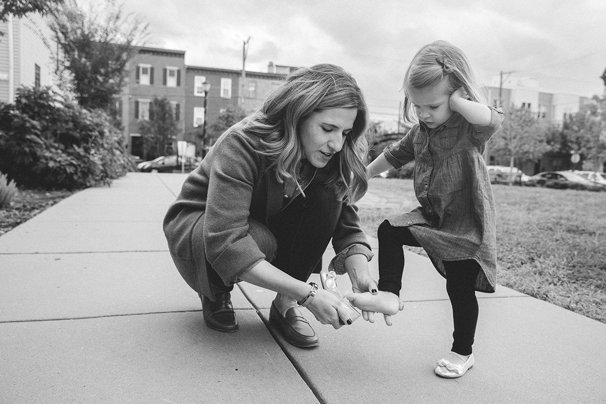 Mother helps daughter put on shoe.
