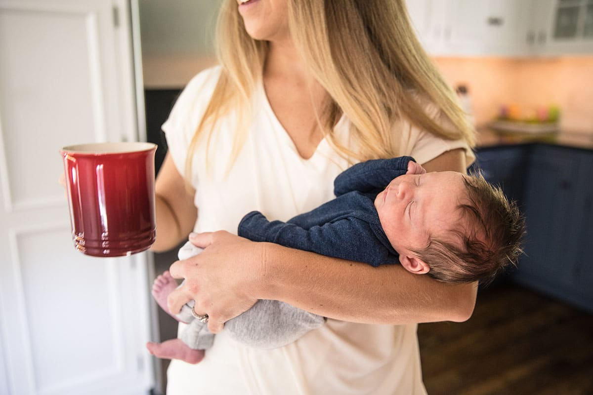 Mother holds cup of coffee and baby.