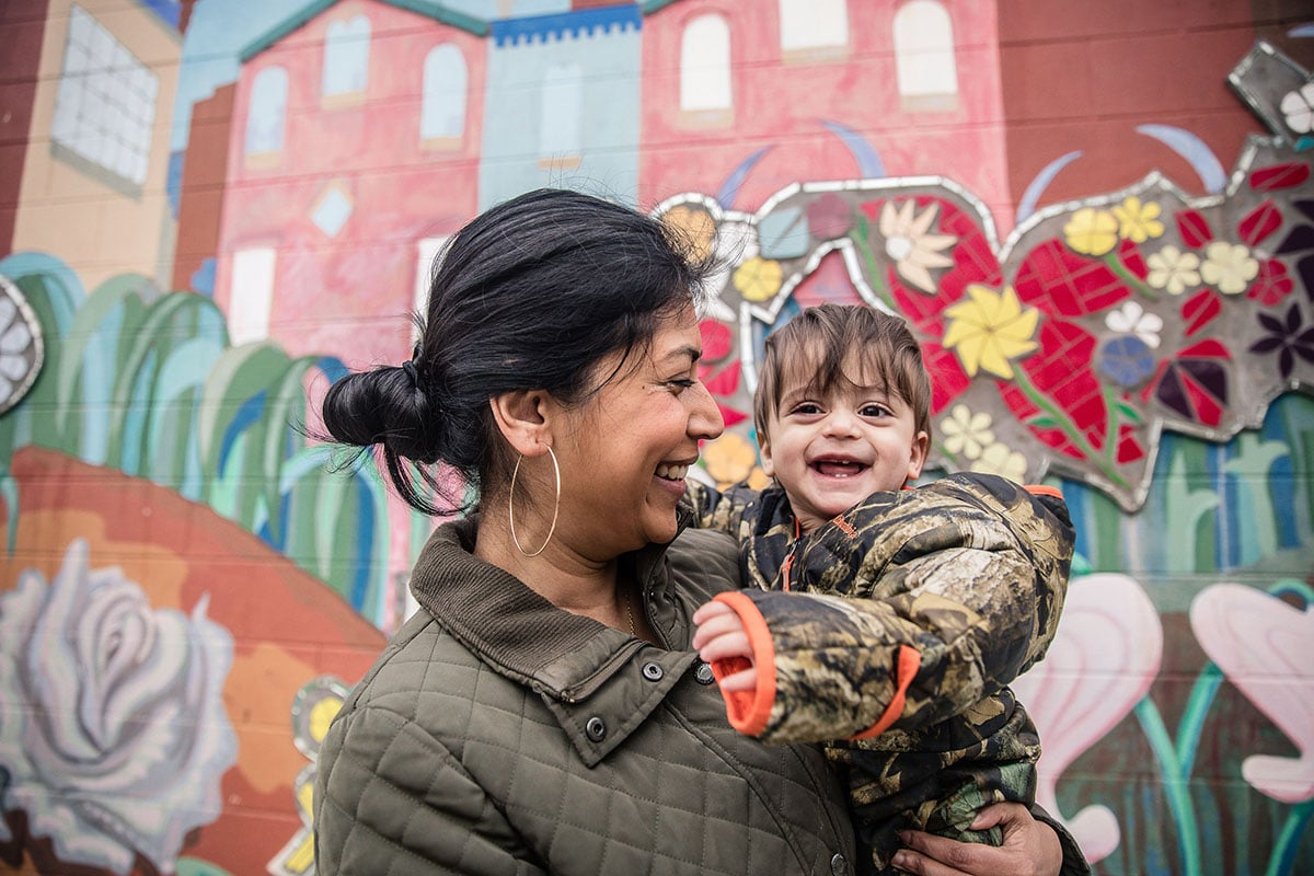 Mother and child standing in front of colorful mural wall in Philadelphia.