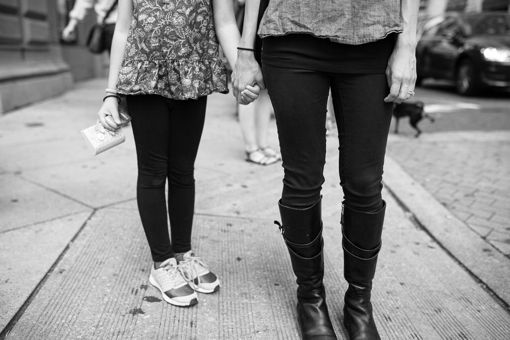 Mother and daughter holding hands in the city.