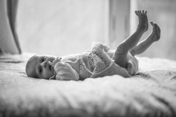 Baby lying on blanket in knit dress.
