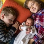 Brother and sister with newborn sibling.