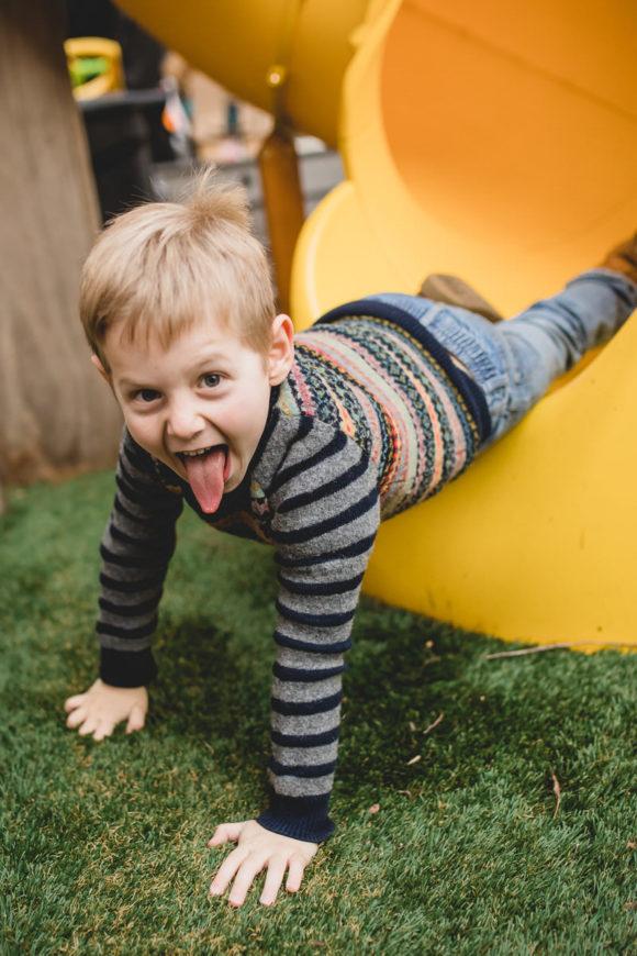 Boy sliding down slide.