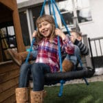 Brother and sister playing on swing.