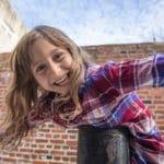 Girl playing outside by Philadelphia brick wall.