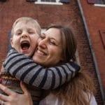 Mother and son hugging outside Philadelphia home.