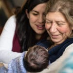 Grandmother holds new granddaughter while daughter looks on.