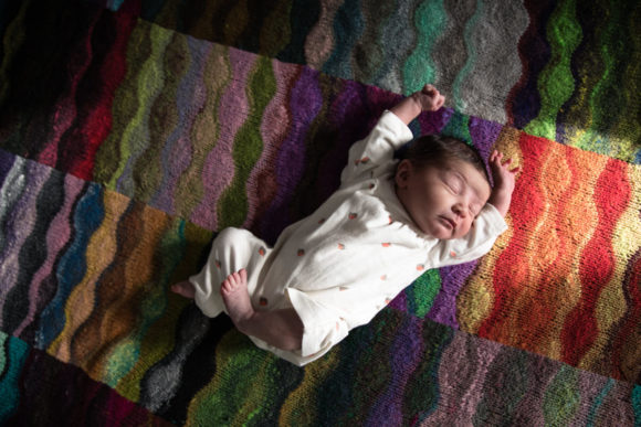 Newborn Baby on Rainbow Blanket