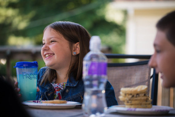 Girl laughing while sitting at table.