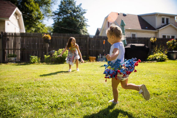 Sisters running on grass in yard.
