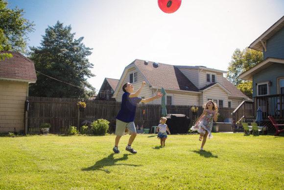 Kids play ball in the yard.