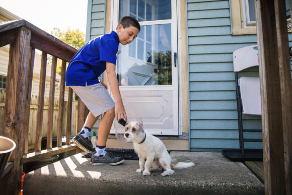 Boy stops to pet dog on porch.