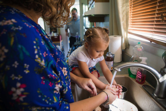 Mother washes daughter's feet in sink.