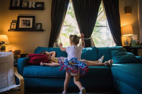 Little girl tackles sister.