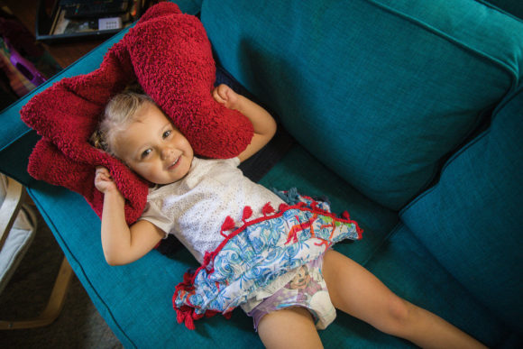 Little girl lays on couch with pillow.