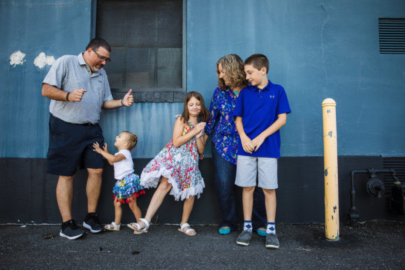 Family dances in front of blue wall.