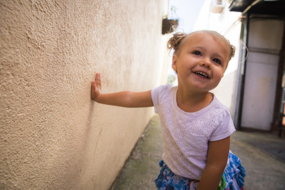 Little girl leans against wall in alley.