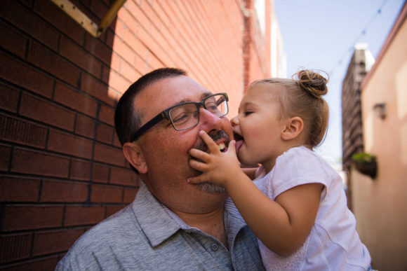 Daughter kisses father's cheek.