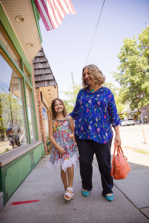 Mother and daughter walk down small town street.