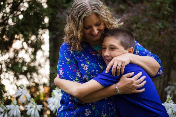 Mother hugs son.