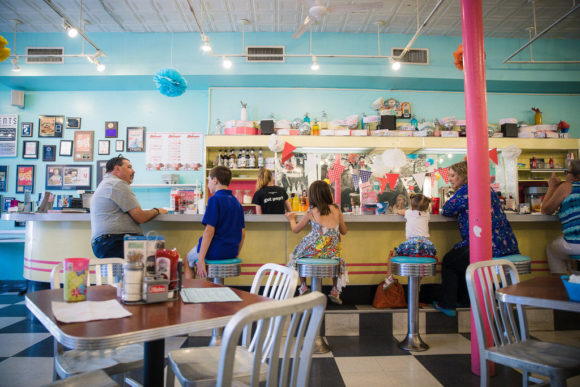 Family sitting at soda fountain counter.