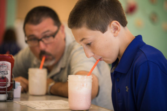 Boy and father drinking milkshakes.