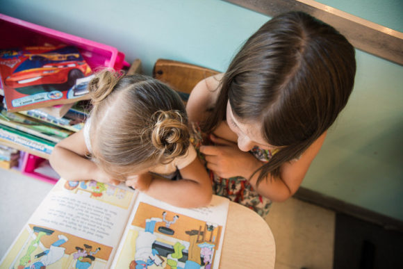 Older sister reads to her younger sister.