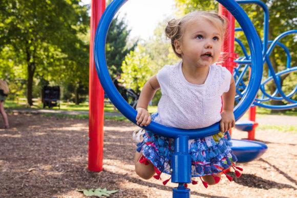 Girl peeks through ring on playground.