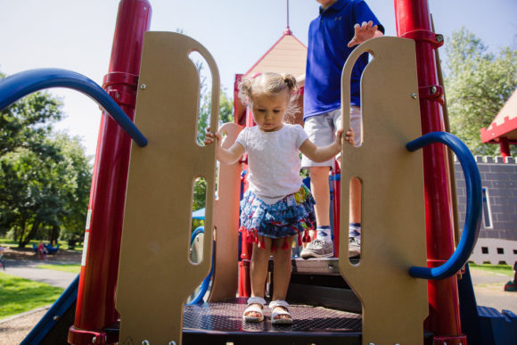 Girl plays with brother on playground.