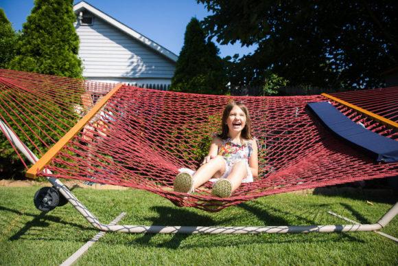 Girl laughing in hammock.