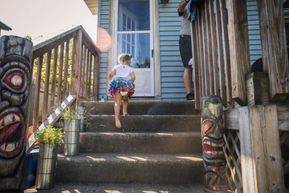 Young girl climbing up porch stairs.
