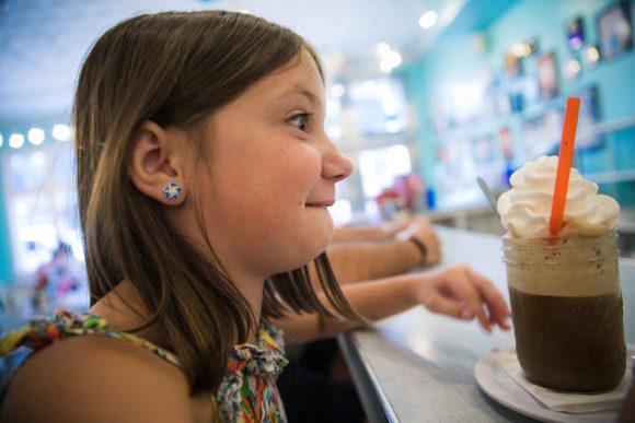 Girl eyes enormous milkshake.